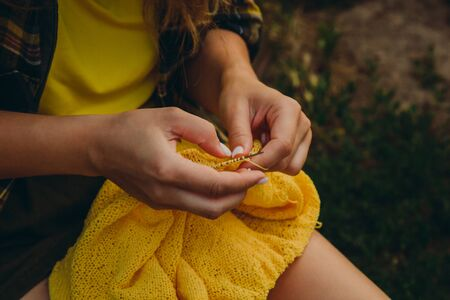 a young girl with long blond hair knits a yellow sweater in the garden in the summer. woman makes clothes with hands closeup.