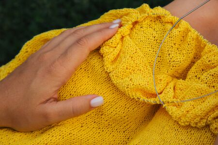 a young girl with long blond hair knits a yellow sweater in the garden in the summer. woman makes clothes with hands closeup. Standard-Bild - 129964825