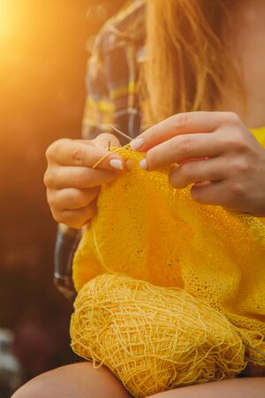 a young girl with long blond hair knits a yellow sweater in the garden in the summer. woman makes clothes with hands closeup. Standard-Bild - 129965410