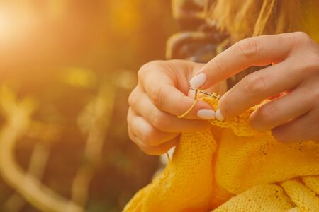 a young girl with long blond hair knits a yellow sweater in the garden in the summer. woman makes clothes with hands closeup. Standard-Bild - 129965599