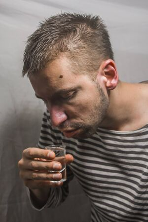 male alcoholism. drinking father, a man drinks vodka. feeling unwell. assault, booze at home. stop alcohol. Stock Photo