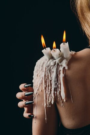 a girl with long hair in the image of a witch is trying to set herself on fire. rituals with candles for love spell and damage. expulsion of a bad spirit from the body.