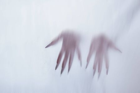silhouette of a female sexual figure behind foggy glass. concept of the spirit of poltergeist from the other world. frightening hands of death through the fabric