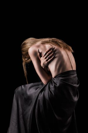 A girl with a bare back, severe thinness and protruding ribs. The concept of anorexia and bulimia, a disease of thin people. The struggle of the evil spirit in a girl, suffering and poverty