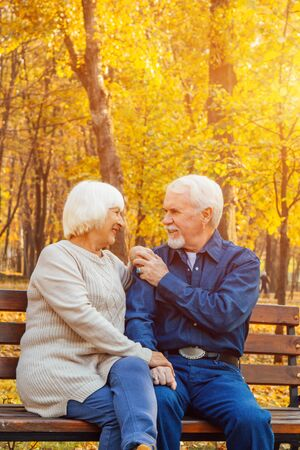 Happy elderly man and woman sitting on a bench in autumn day. Relaxed senior couple sitting on a park bench. Grandfather gently kisses grandmother on the forehead