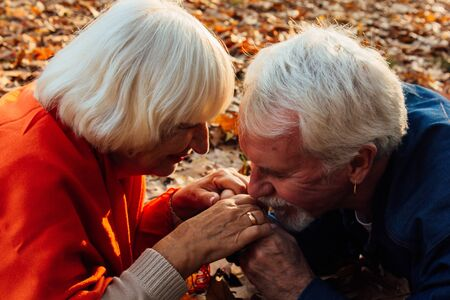 Close up portrait of a happy old man kissing his wife's hands. In the park in autumn foliage a happy couple is resting