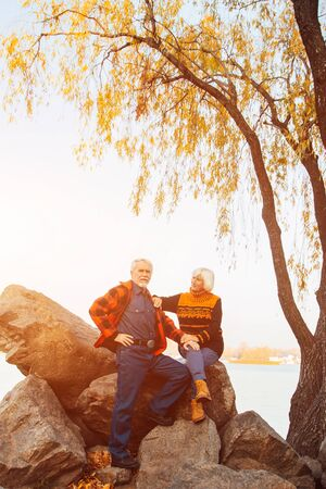 Cheerful elderly people a woman and a man are sitting on the stones and hugging on the lake, against the background of the bridge