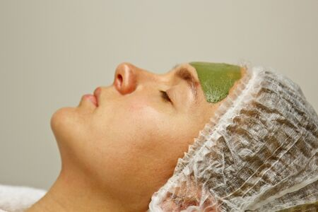The concept of cosmetology. Close-up of a beautician applying a green mask with a brush on a woman's face