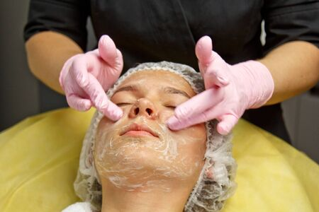 concept beautician. The hands of a cosmetologist put cream on the face of a woman. Beautician applies a cream to the face of the girl