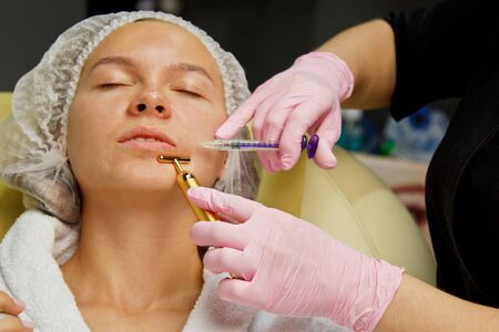 contour plastic. A cosmetologist injects a botulinum toxin to tighten and smooth out wrinkles on the skin of a female face
