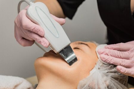 close-up. Ultrasonic face cleaning. Modern equipment. Beautician does cosmetic procedure on woman face