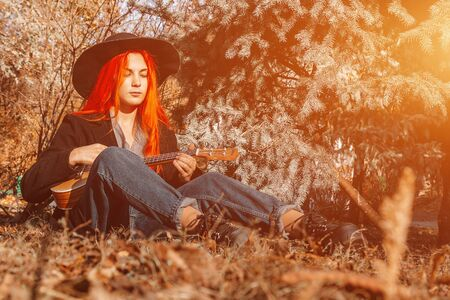Sexy redhead girl with long hair plays the ukulele. Perfect woman portrait. Gorgeous strong and thick hair. Deep blue eyes. Natural beauty, clean skin, face and hair care