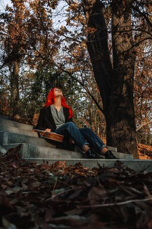 Sexy beautiful redhead girl with magnificent long hair. Ukulele playing, sitting on the steps in the park. Perfect woman portrait. Musical education, street performer