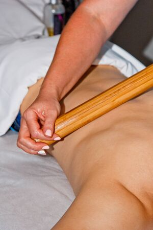 Wellness concept. Professional masseur gives a man a Thai massage with bamboo sticks at the spa. Relaxation and recovery after work Banco de Imagens