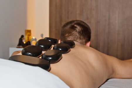 Wellness concept. Handsome young man relaxing under the stimulating effect of a traditional hot stone massage in a luxury spa and wellness center. Recovery after work Banque d'images