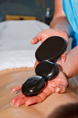 Wellness concept. Handsome young man relaxing under the stimulating effect of a traditional hot stone massage in a luxury spa and wellness center. Recovery after work Stock Photo