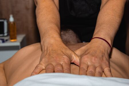 Female professional masseur makes therapeutic therapeutic back massage with hands to male athlete. woman massages a man.