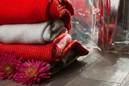 Pattern of colorful knitted sweaters closeup. Handmade merino wool product. A stack of folded clothes with flowers