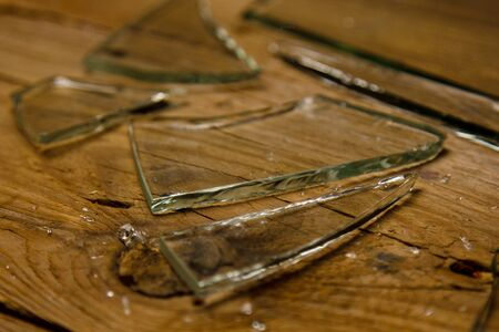Broken glass on an old wooden floor, concept of violence