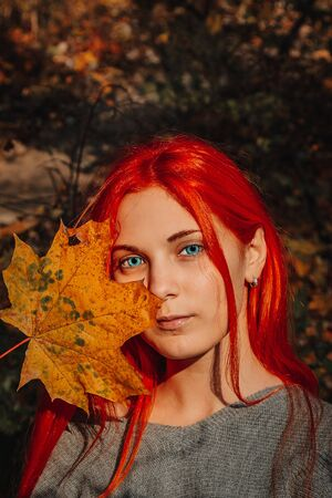 Sexy beautiful redhead girl with long, strong and thick hair. Perfect woman portrait on a background of autumn foliage. Gorgeous deep blue eyes. Natural beauty, clean skin, face and hair care