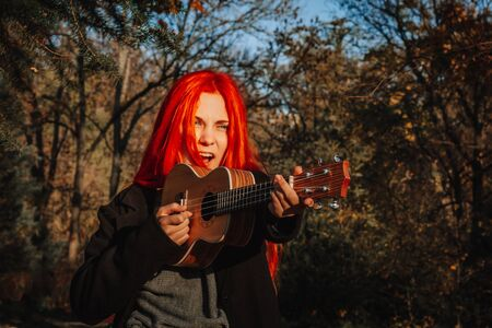 Red-haired girl with long hair plays on the ukulele in the park. School, music education concept, student learns to play the string instrument. Hands of a musician, classical, melody, creativity