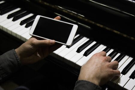 two male hands on the piano with a smartphone. palms lie on the keys and play the keyboard instrument in a music school. student learns to play. hands of a pianist. black dark background Stockfoto