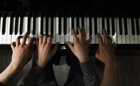 playing four male hands on the piano. palms lie on the keys and play the keyboard instrument in a music school. student learns to play. hands of a pianist. black dark background
