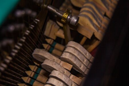 Close up of old broken dusty piano from the inside. Hammers in abandoned piano striking strings. Music playing from the ancient ruined piano. Gavel of the string open mechanism