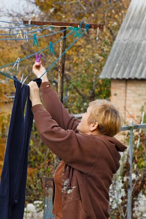 Laundry woman hangs clean wet cloth on clothes dryer after washing at home. Household chores and housekeeping