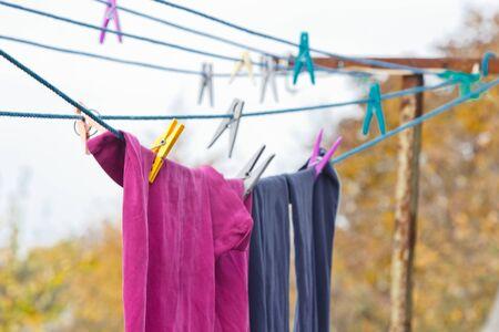 An der Wäscheleine hängt eine Wäscheklammer. Ein Seil mit sauberer Wäsche und Kleidung im Freien am Tag der Wäsche. Vor dem Hintergrund grüner Natur und Himmel