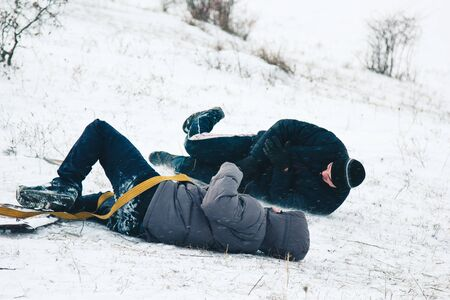 Two friends have fun and enjoy the fresh snow on a beautiful winter day. Snowfall falling in the snow Banco de Imagens