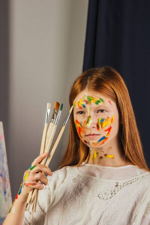 The young girl of the artist in a light white dress, paints a picture on canvas in the workshop. The face is stained with paints. A young student uses brushes, canvases and easels. Creative work