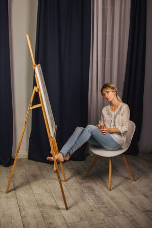Young artist girl in a white shirt and blue jeans, paints a picture on canvas in the workshop. A young student uses brushes, canvases and easels. Creative work for children and adults Banco de Imagens