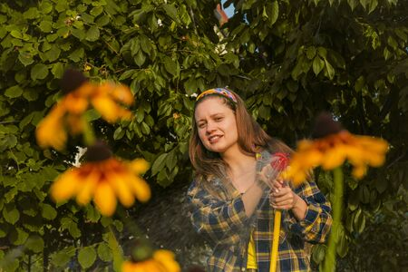 young pretty girl having fun in the garden watering plants with a hose. Smiling while taking a favorite hobby