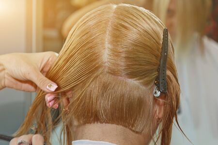 Woman with medium long blonde hair. With a short haircut at the hairdresser at the stylist using scissors. Care procedures. The master shortens his hair