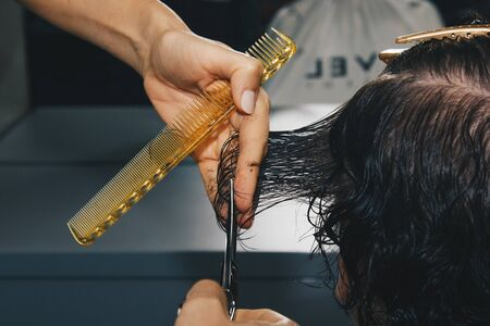 Closeup of a hairdresser cuts the wet brown hair of a client in a salon. Hairdresser cuts a woman. Side view of a hand cutting hair with scissors Фото со стока