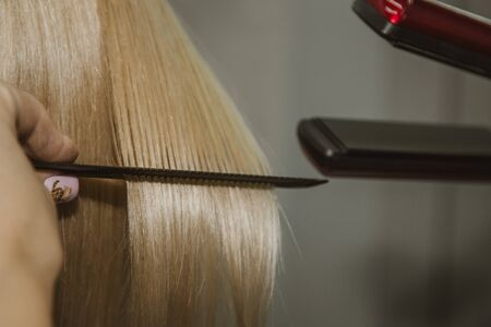 Hairstyle. Attractive blonde with short hair does a hairstyle with an electric iron. Hair straightener gray background. close-up. Macro photo 스톡 콘텐츠