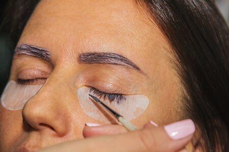 Beauty treatment. Closeup woman's face with paint on eyelashes. laminating eyelashes. Side view