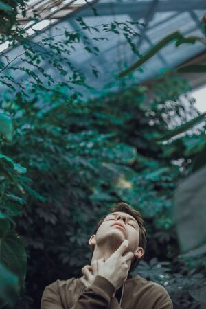 Portrait of a young man in green leaves. A good guy is standing against a wall of green plants. Close-up concept of sore throat 版權商用圖片