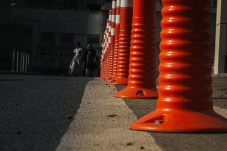 A barrier made of plastic columns with reflective pigment on an asphalt road. Pillars dividing opposite lanes to ensure traffic safety. Danger concept