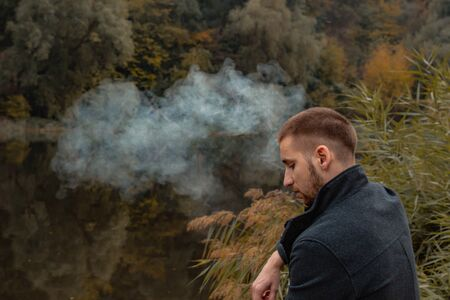 A guy with a beard sits on the lake and smokes an electronic cigarette. Blows puffs of smoke. The concept of unity with nature. Rest near the water. Vape, Man Vaping. lips and smoke, a lot of smoke Фото со стока
