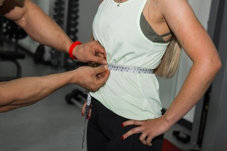 weight loss, personal trainer, nutritionist, fitness, motivation, healthy lifestyle. A man measures the waist of a girl with a tape measure. Close up, macro photo. Preparation for training