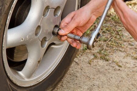Service process. A man holds a tire in the garage. Replacing winter and summer tires. Seasonal tire replacement concept