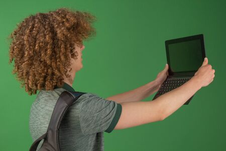 A young student in jeans clothes with a backpack holding a laptop in his hands. Isolated on a green background. Studying at the university online. Video communication. Quarantine