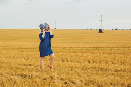 Young beautiful blonde girl in the middle of a wheat field. Posing looking at the camera. Summer landscape, good weather. Blue cotton dress, eco style. Beautiful striped hat