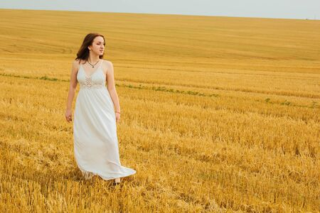 Good outdoor recreation. Young beautiful redhead woman in the middle of a wheat field, having fun. Summer landscape, good weather. Windy day with the sun and clouds. White cotton dress, eco style