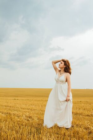 Good outdoor recreation. Young beautiful redhead woman in the middle of a wheat field, having fun. Summer landscape, good weather. Windy day with the sun and clouds. White cotton dress, eco style Banque d'images