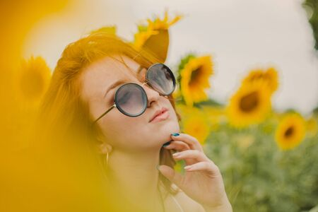 Portrait of a beautiful, cute, red-haired girl in a white dress and glasses. Walks in the sunflowers. Emotion of pleasure, freedom concept, lifestyle. Sunglasses advertising