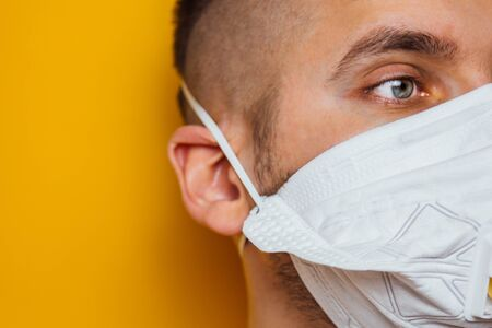 Close up photo of a young bearded white man with a medical face mask during coronavirus quarantine. The front part of the face lightly blurred. Coronavirus, COVID-19 outbreak. Doctor, nurse concept