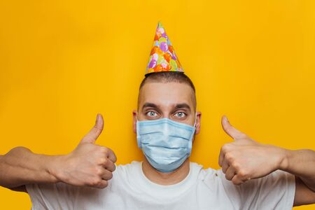 Young Caucasian guy in a medical mask celebrates his birthday. Shows thumbs up. Sad depressed without friends due to the outbreak of the coronavirus epidemic
